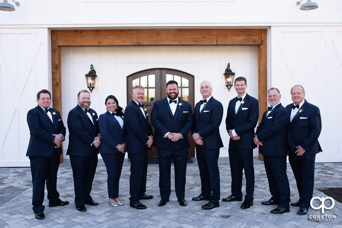 Groom and groomsmen in front of a white barn.