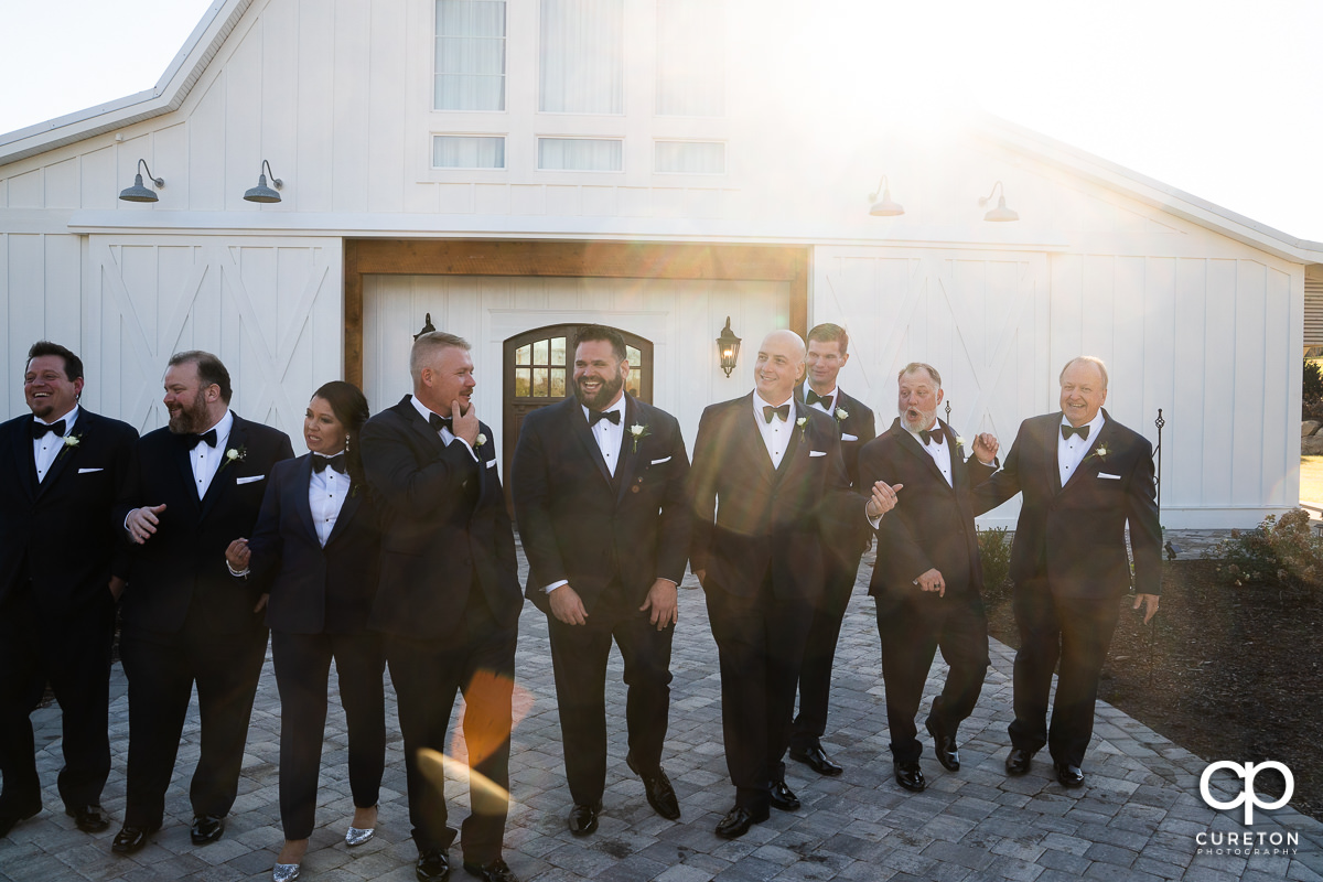 Groom and groomsmen standing in warm sunlight.