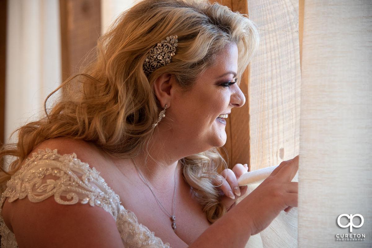 Bride peeking out a window.