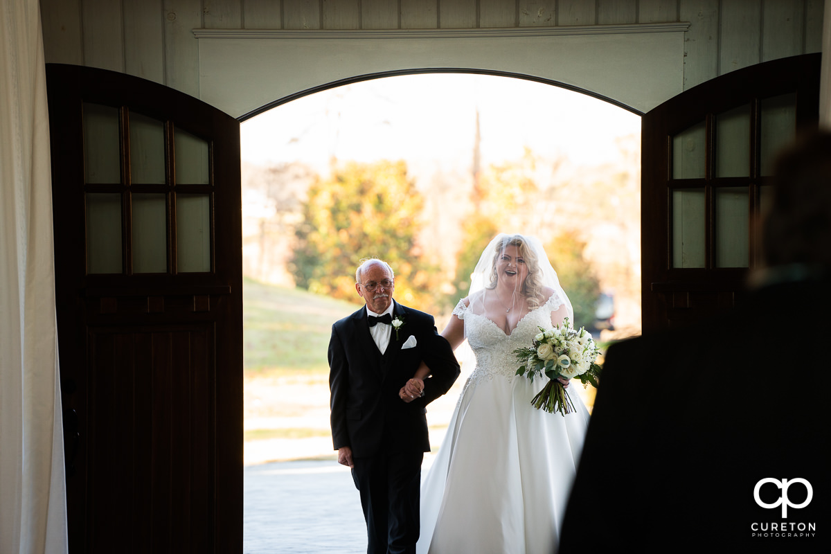 Bride being walked down the aisle.