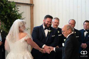 Groom shaking his bride's dad's hand.