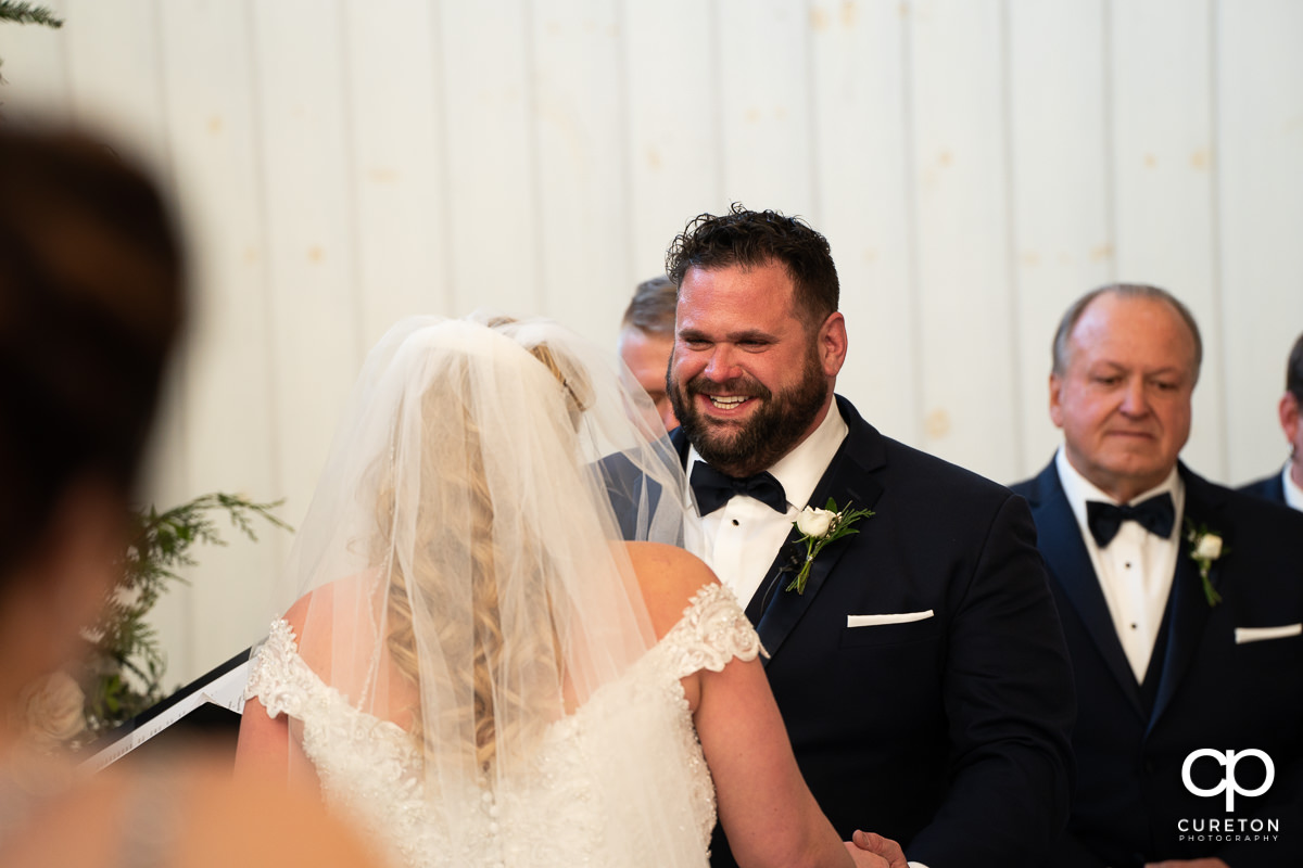 Groom smiling at the alter.
