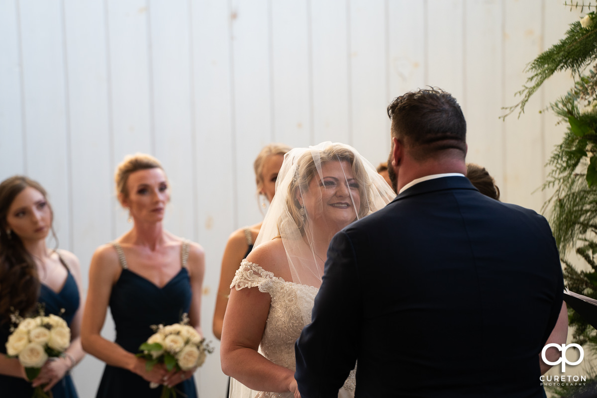Bride smiling at the alter.