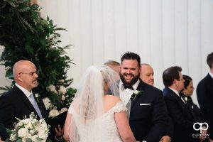 Groom smiling during his vows.