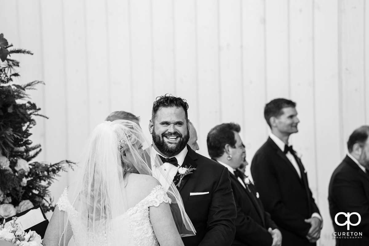 Groom laughing at the alter.
