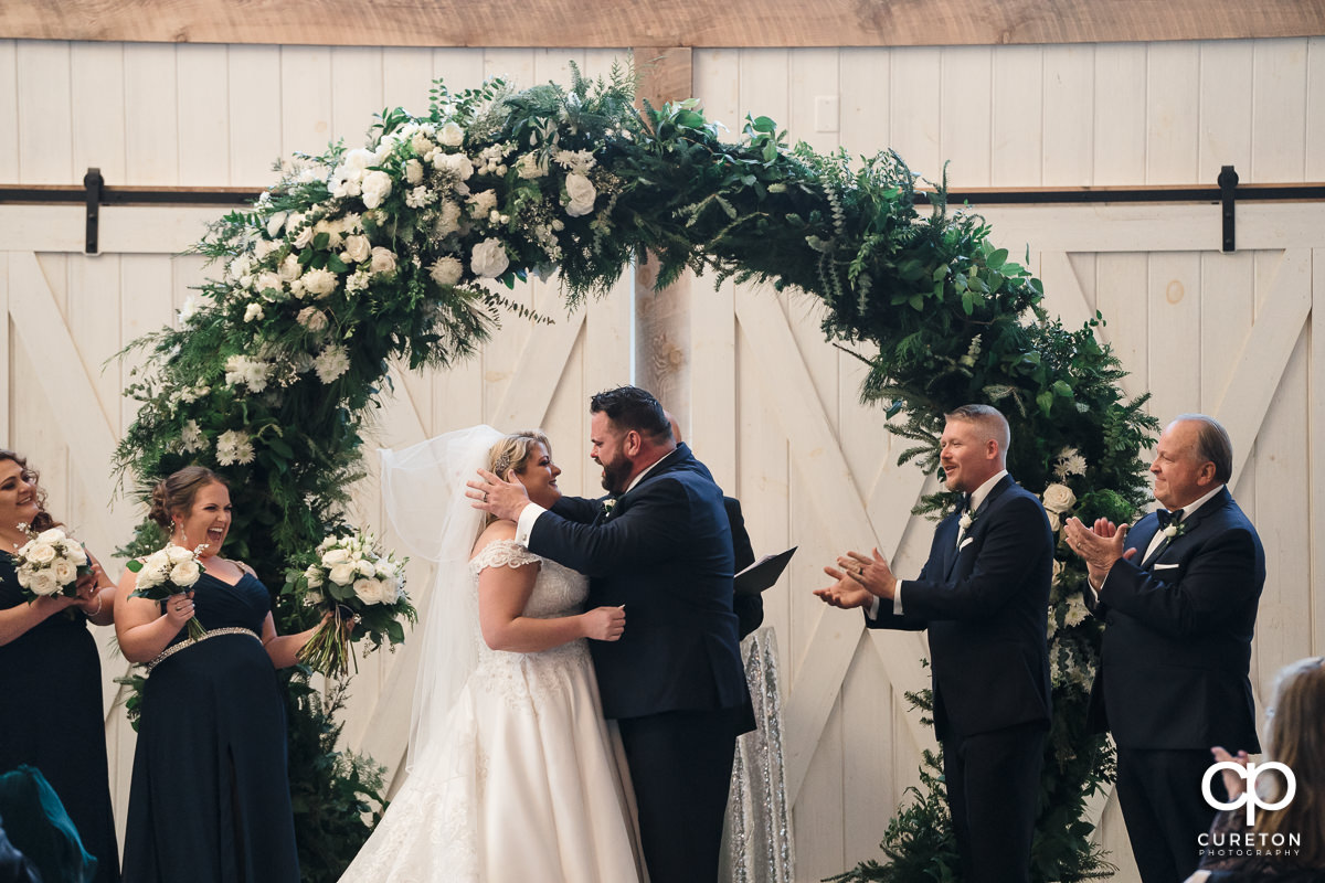 Groom kissing his bride at the alter.