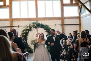 Bride and groom dancing back up the aisle.