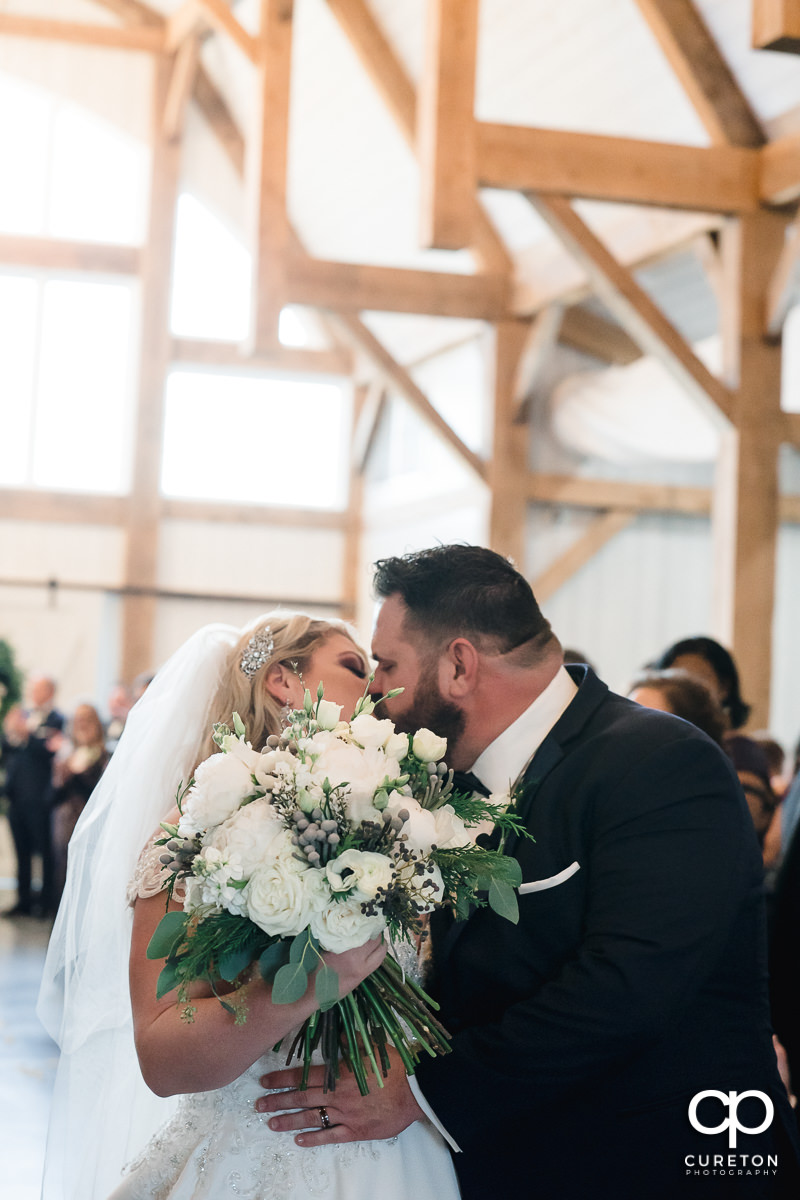 Groom kissing his bride in the aisle.