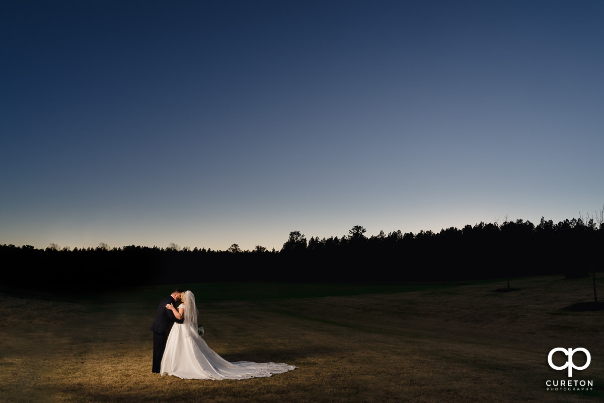 Bride and groom dancing in a field at sunset.