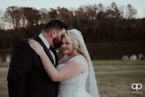 Groom whispering into his brides ear.