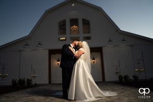 Bride and groom kissing in front of Heyward Manor at sunset.