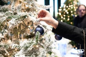 Wedding guest hanging an ornament n a tree.