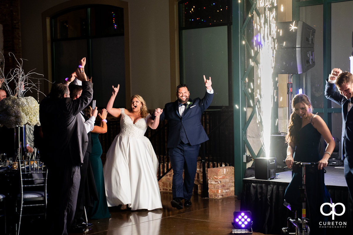 Bride and groom making an entrance into the wedding reception with spark fountains.
