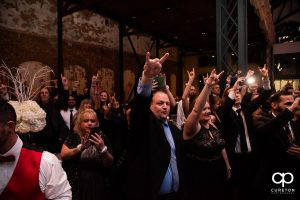 Wedding guests cheering the arrival of the couple.