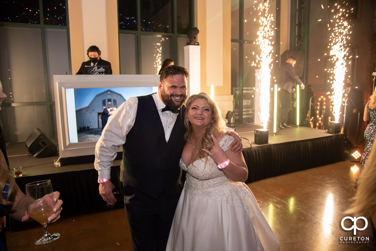 Bride and groom in front of spark fountains.