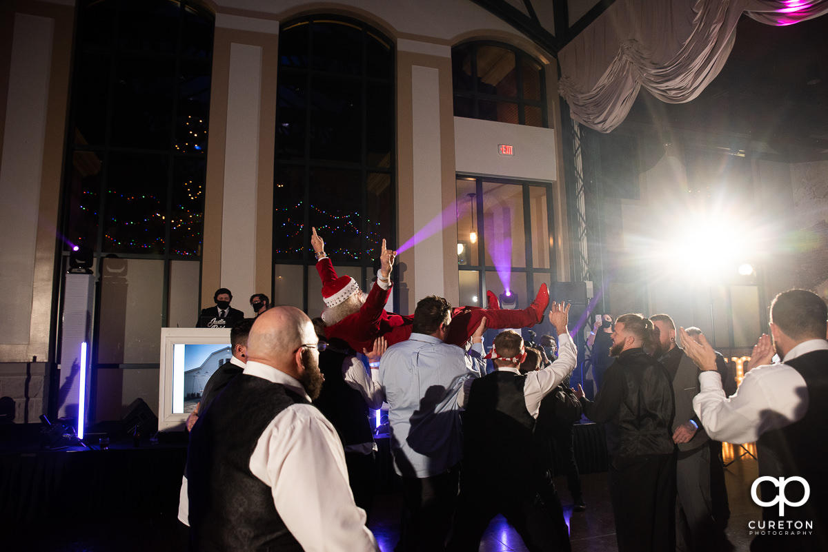 Santa claus crowd surfing at the wedding reception.