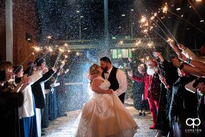 Bride and groom having a grand exit with sparklers and snow.