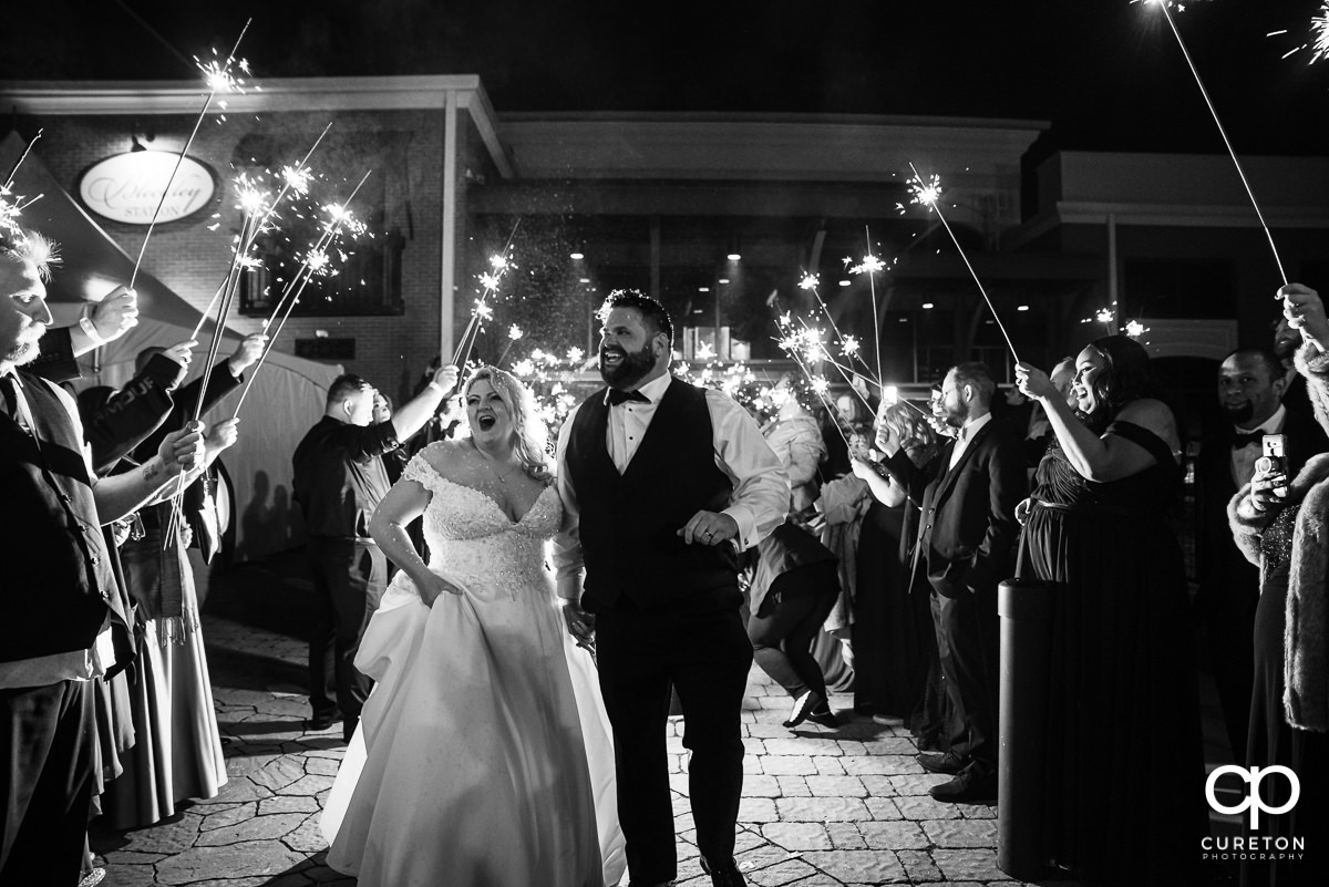 Bride and groom having a grand exit with sparklers .