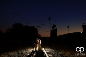 Bride and groom on railroad tracks near Fluor Field at sunset.