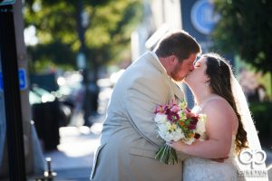 Bride kissing groom on Main St. in downtown Greenville,SC.