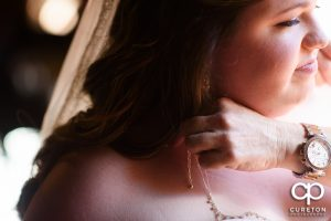 Bride putting on her jewelry.