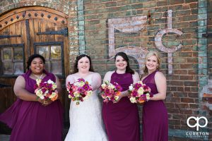 Bride and Bridesmaids standing on the deck of the Old Cigar Warehouse.