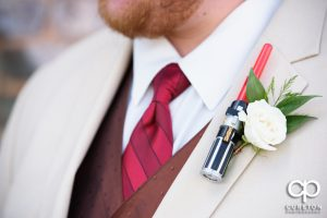 Closeup of Star Wars themed lightsaber boutonniere for the wedding.