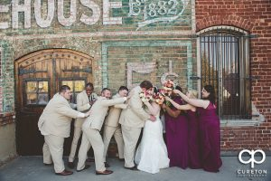 Creative wedding party pose on the deck at The Old Cigar Warehouse in Greenville,SC.