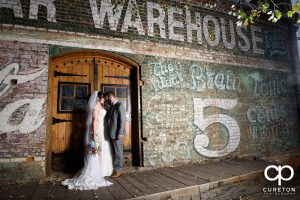 Bride and groom on the back deck during their wedding reception at Old Cigar Warehouse.