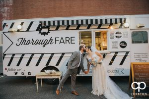 Bride and Groom kissing in front of the Thorough Fare food truck.