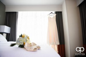 Bride's dress hanging in the window of Embassy Suites River Place.