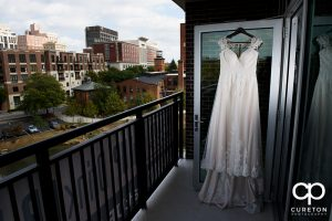 Bride's dress hanging in the window of Embassy suites overlooking downtown Greenville.