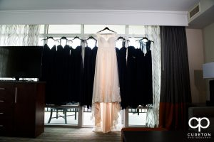 Bride's dress hanging with the bridesmaids dresses.