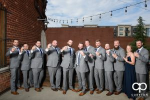 Groom and groomsmen having a drink on the deck of the old cigar warehouse.