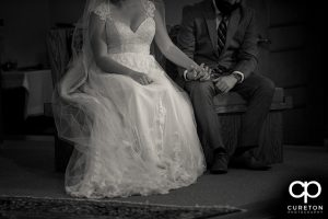 Bride and groom holding hands during the ceremony.