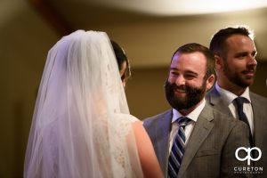 Groom smiling at his bride during the wedding ceremony.
