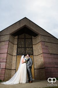 Bride and groom kissing outside of Saint Anthony's in downtown Greenville South Carolina.