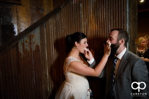 The bride and groom smashing cake on each other's face.