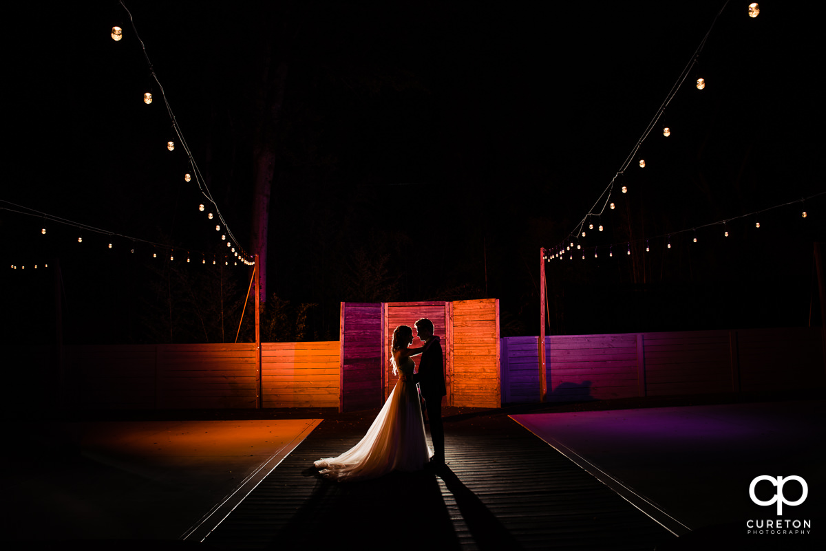Bride and groom in front of orange and purple lights in the courtyard of The Rutherford at their wedding reception.