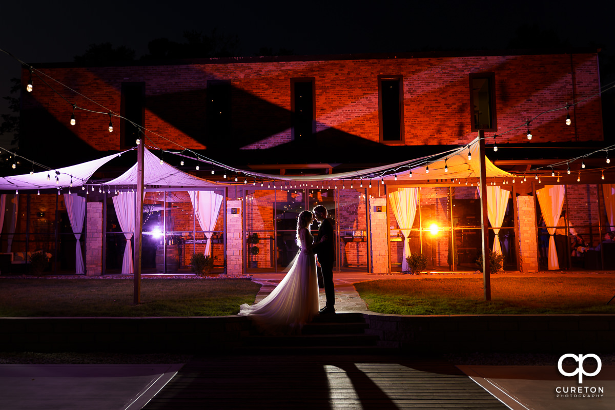 Bride and groom standing in front of The Rutherford wedding venue at night.