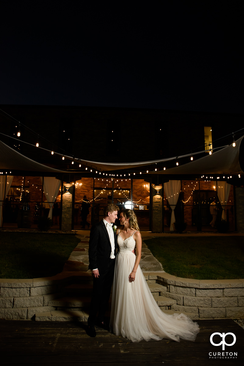 Bride and groom outside of their wedding reception at The Rutherford at night.