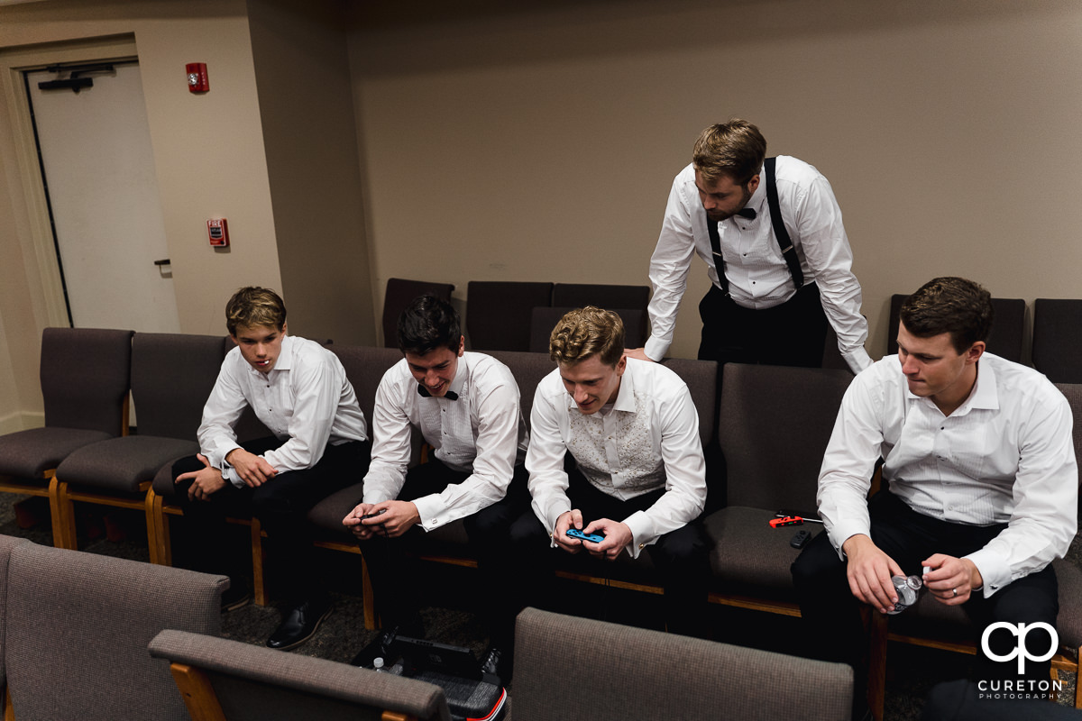 Groom and groomsmen playing video games.