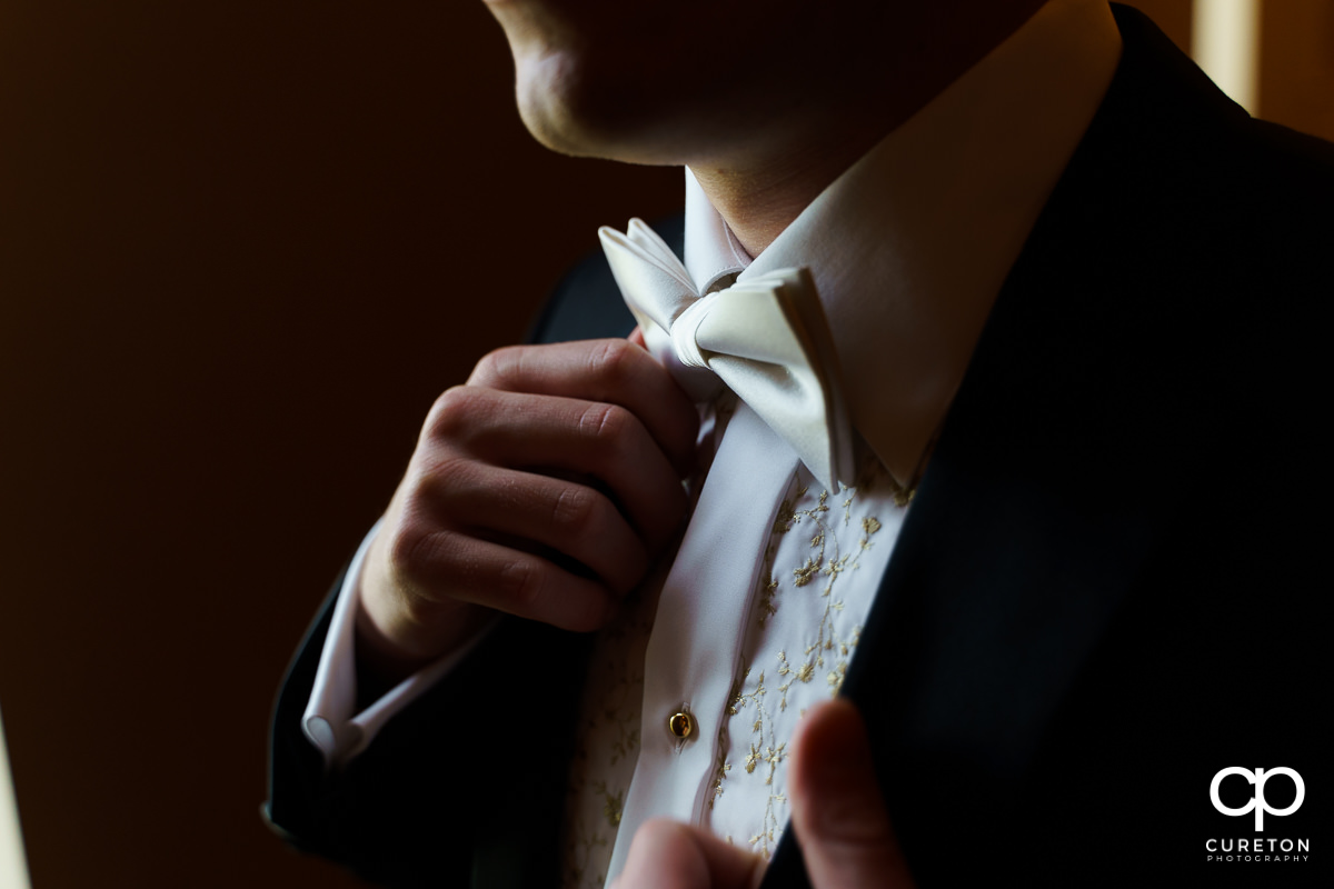 Groom adjusting his tie.