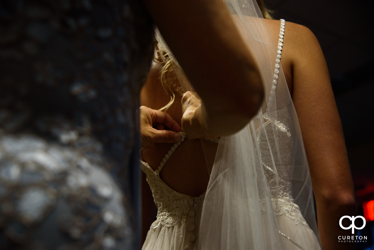 Bride having her dress zipped.