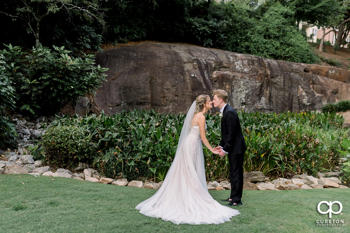 Bride and groom kissing in the Rock Quarry Garden.