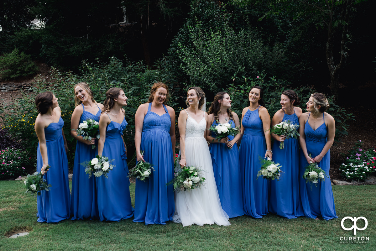 Bridesmaids laughing in the park.