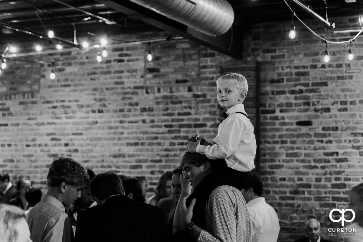 Boy on his dad's shoulders at the reception.
