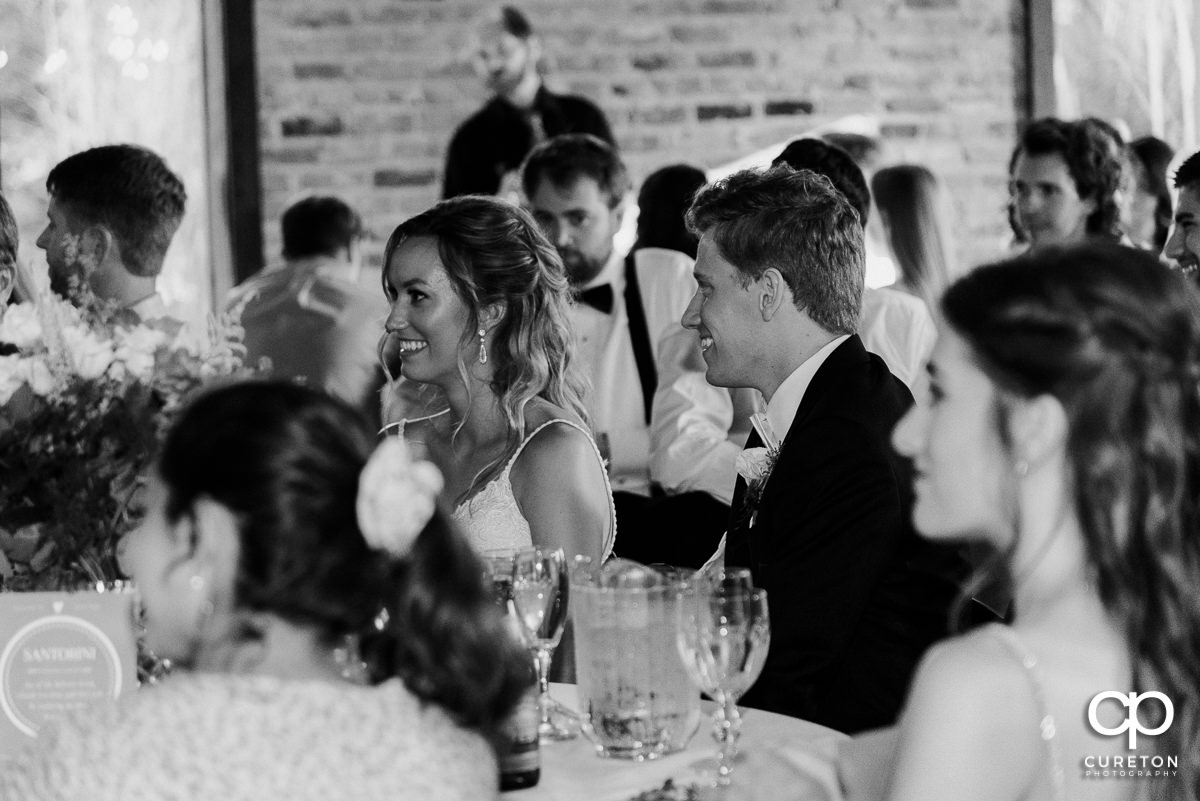 Bride and groom listening to a toast at the reception.