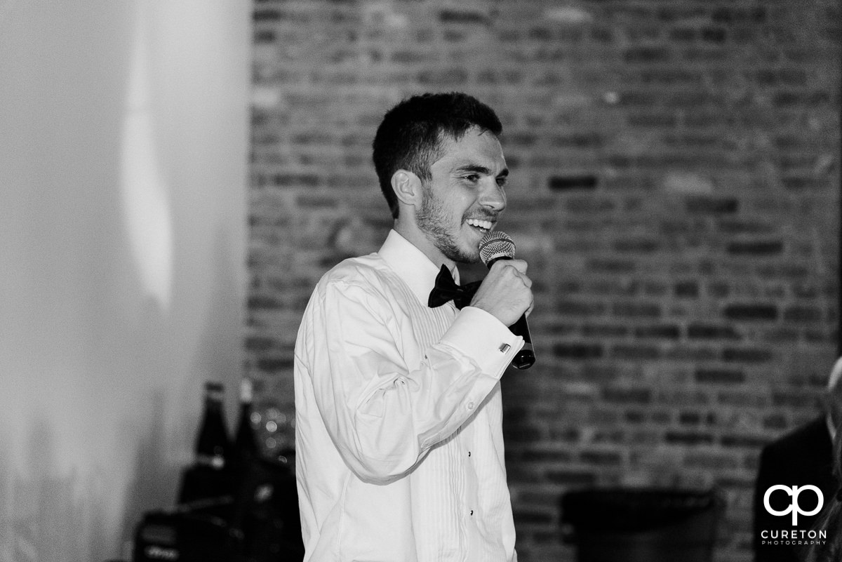 Best man smiling while giving a speech.