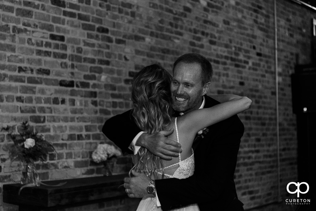 Bride's dad hugging her after they shared a dance.